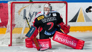 Svartklädd ishockeymålvakt med röda benskydd står på knä.