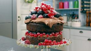En chokladkaka fylld med bär, toppad med färskostfrosting och färska bär.