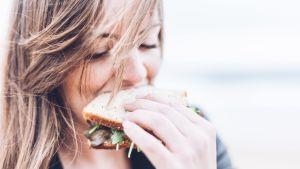 Nainen syö voileipää.