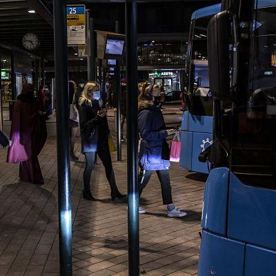 Ihmisiä nousemassa bussiin Elielin aukiolla.