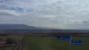 Vy över en slätt i västra Kosovo med berg i bakgrunden.