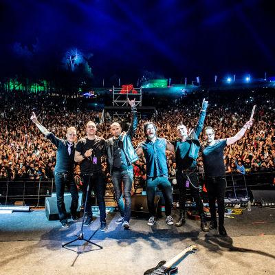 Ett rockband på scenen med publikhav i bakgrunden.