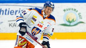 Vitklädd ishockeyspelare från Tappara ler in i kameran.