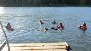 Fyra personer flyter i vattnet.