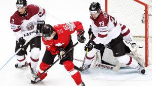 Hockeyspelare kämpar om pucken framför målburen.
