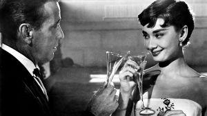 Humphrey Bogart ja Audrey Hepburn kliistävät puolilähikuvassa. Kuva elokuvasta Kaunis Sabrina.