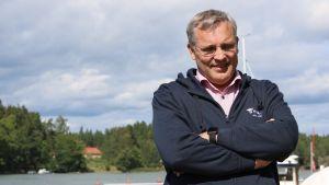 Mikael Pentikäinen står iklädd en mörkblå luvtröja vid vattnet.