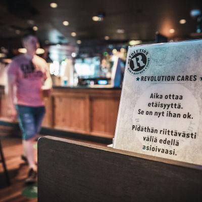 """""""Aika ottaa etäisyyttä. Se on nyt ihan ok"""" -korona ohjeistus ravintola Revolutionissa Jyväskylässä."""