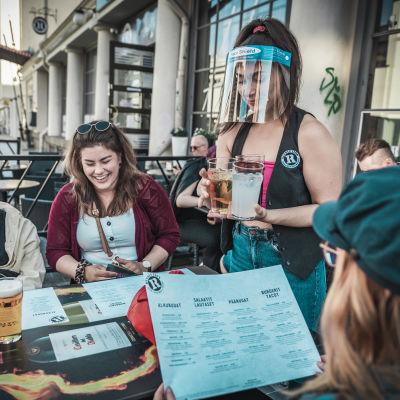 Vuoropäällikkö Maral Yadegarian tarjoilee juomia pöytään Visiiri kasvoillaan Jyväskylän Revolutionissa.