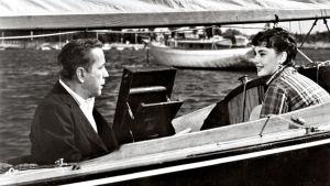 Humphrey Bogart ja Audrey Hepburn istuvat purjeveneessä. Kuva elokuvasta Kaunis Sabrina.