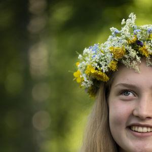 En glad flicka med en blomsterkrans i håret.