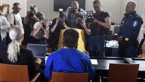 Den yngre brodern täckte sitt ansikte inför pressfotograferna.