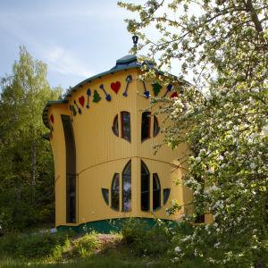 vy över bladhuset utifrån, som är format som ett blad, är gult och har små spadar, hjärtan och granar som träfigurer runt byggnades tak.