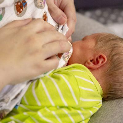 6 päivän ikäinen tyttö imee rintaa imetystyynyn päällä.