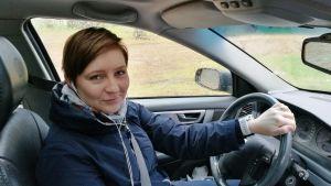 Katja Palosaari kör bil och lyssnar på radio.