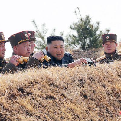 Nordkoreanska medier har under den här månaden visat bilder av hur Kim Jong-Un har omgärdats av höga officerare utan ansiktsmasker. Det anses bevisa att den högsta ledningen i landet har testats för coronaviruset.