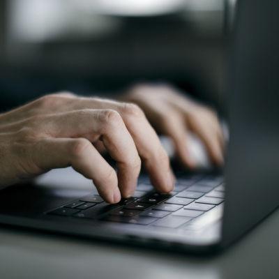 Närbild av händer spm skriver på en dator, laptop.