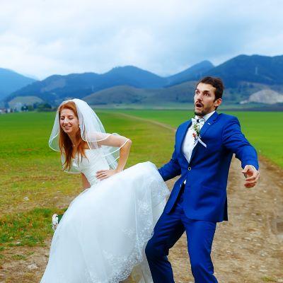 kvinna i brudklänning lutar sig framåt och ler, man i blå kostym ser förskräckt ur