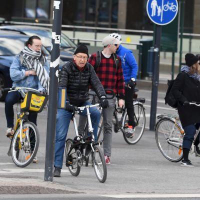 Flera cyklister står och väntar vid en korsning.