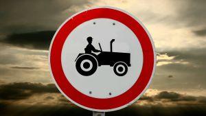 Skylt av en bonde som kör traktor. Mörka moln i bakgrunden.