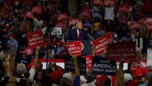 President Donald Trump står vid ett podium i ett folkhav under ett kampanjmöte. Folk håller skyltar i händerna där det står Make America Great Again.