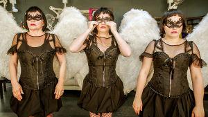 Näyttelijättäret rivissä enkelinsiivet ja mustat pitsivaatteet päällään.