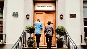 """Kaj Korkea-aho och Kjell Westö går med ryggen vänd mot kameran upp för trappan till Abbey studios dörr. Ovanför dörren står det Abbey Road  Studios""""."""