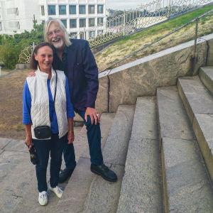 Saga Eriksson-Ahjolinna (t.v.) och Aku Ahjolinna står på en trappa vid Uspenskijkatedralen i Helsingfors. Aku håller Saga om axeln och bägge ser glada ut.