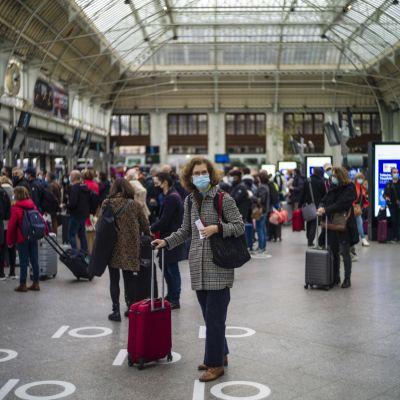 Juna-asema on täynnä ihmisiä, jotka haluavat kaupungista pois ennen ulkonaliikkumiskiellon alkamista.