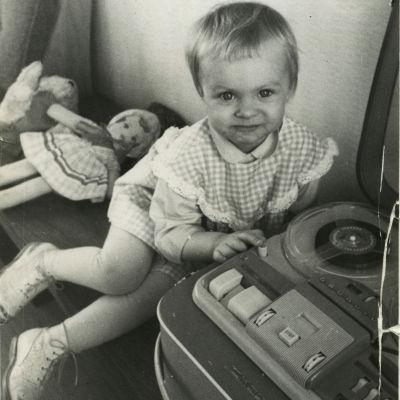 Kaksivuotias Sara Paavolainen nojaa isänsä Grundig magnetofoniin. Taustalla nukke ja nalle.