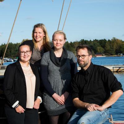 Fyra personer ombord på en allmogebåt som ligger vid en brygga.