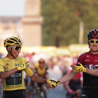 Egan Bernal och Geraint Thomas cyklandes hand i hand och pekandes på varandra.