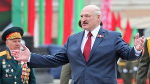 Lukashenka levittää käsiään hymyillen. Hänellä on tumma puku, punainen kravatti. Taustalla seisoo vanha mies univormussa.