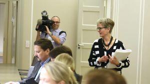 Vuokko Piekkala (till höger i bilden) träffar parterna under poststrejken. I bakgrunden syns en TV-fotograf.