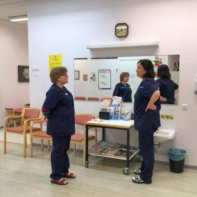 Två vårdare står och pratar i väntrummet
