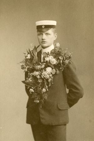 Carl Nymans studentfoto där han står med allvarlig min och en enorm blomsterklass runt halsen.