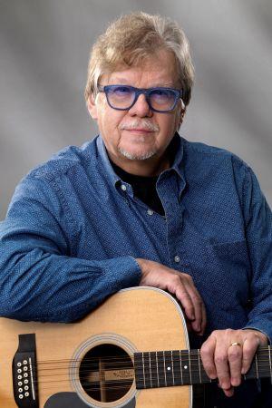 Mikko Alatalo poseeraa sinisissä laseissaan ja kitaran kanssa. Kuva on otettu 2020 vuoden paikkeilla.