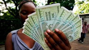 Kvinna i Zimbabwe håller upp nya sedlar med valören 10 triljoner i januari 2017. En triljon är det samma som en miljard miljarder.