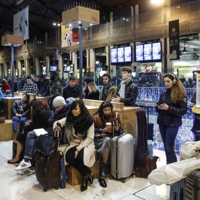 Massvis med människor sitter och väntar på sina tåg i en tågstation.