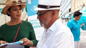Anna-Liisa Tilus juttelee miehen kanssa.