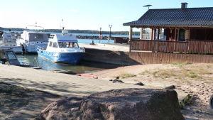 några båtar vid en brygga i Borgå skärgård. I bakgrunden ett hus, i förgrunden en sten och sandstrand