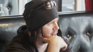 Musikern Aki Tykki sitter vid restaurangbord intill stort fönster.