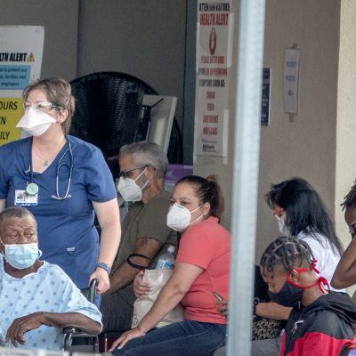 Folk i Florida väntar på att få komma in på ett sjukhus. Alla bär ansiktsskydd.