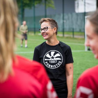 Joukkueenjohtaja Heli Backman puhuu Ponnistuksen tyttöjengille.