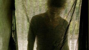 Silhuett av person står bakom ett skynke och tittar ner i marken