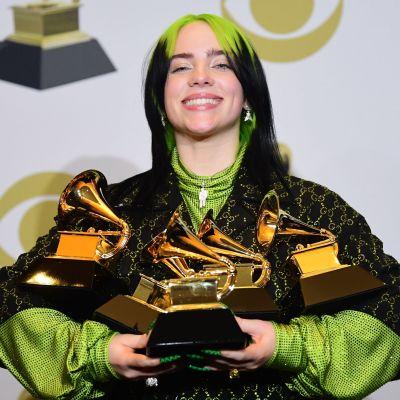 Billie Eilish poserar med sina fem grammypriser som är formade som grammofoner i famnen.