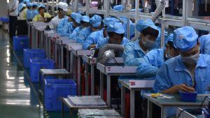 Blåklädda kinesiska fabriksarbetare med munskydd sitter i rad och jobbar