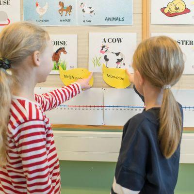 Lapset osoittavat kuvaa seinällä.