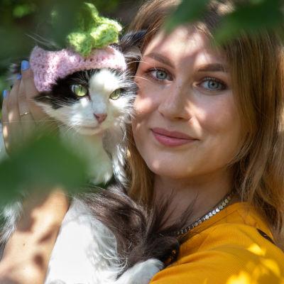 Heli Montonen ja Mauri-kissa puutarhassa.