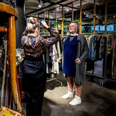 Helena Opas och Lotta Palmgren går igenom kläder i butiken Vaatepuu